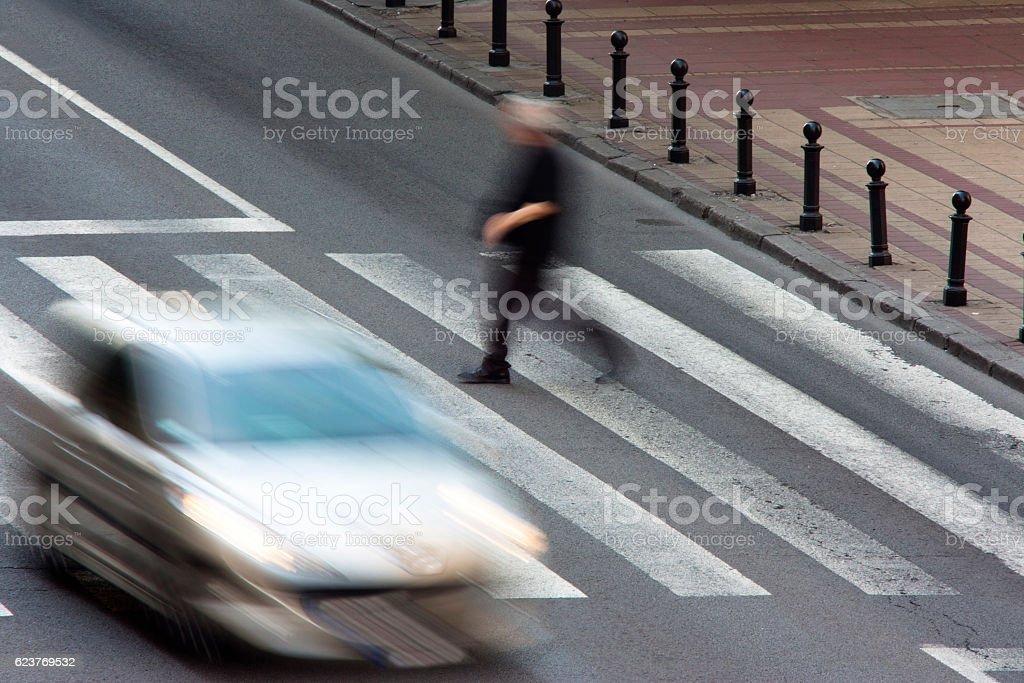 Pedestrian and a driving car on zebra crossing stock photo