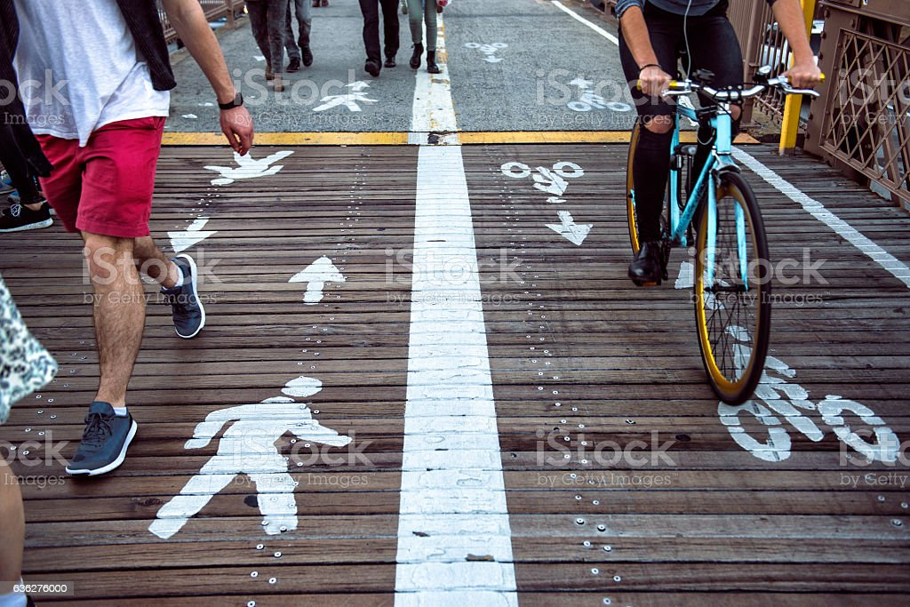 Pedestrian and bicycle riders sharing the street lanes stock photo