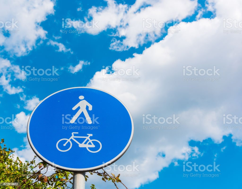 Pedestrian and bike sign under a cloudy sky stock photo
