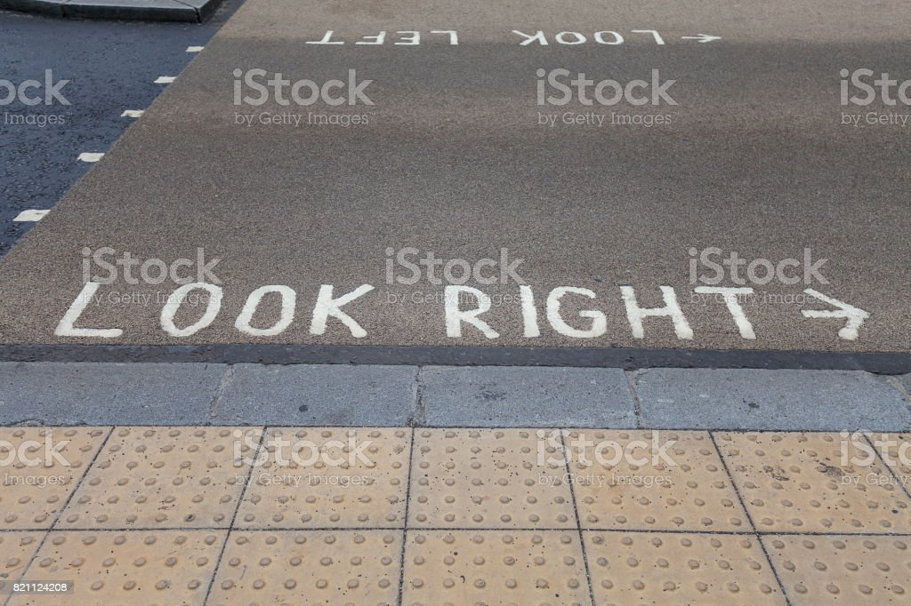 Pedestrian crossing, left side traffic, iinstruction painted on the street, London, United Kingdom stock photo
