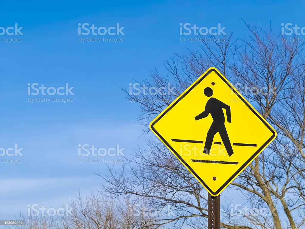 Pedestrian crossing sign with bare trees and sky in background royalty-free stock photo