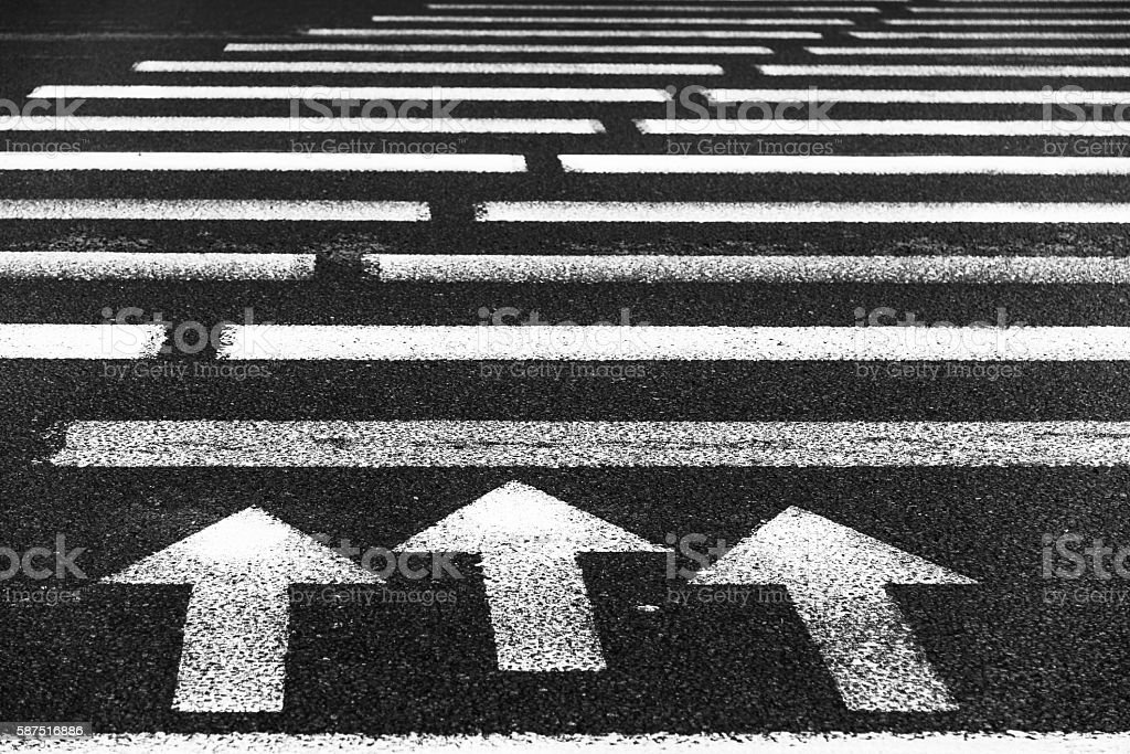 Pedestrian crossing with road marking: white arrows and rectangles  asphalt stock photo