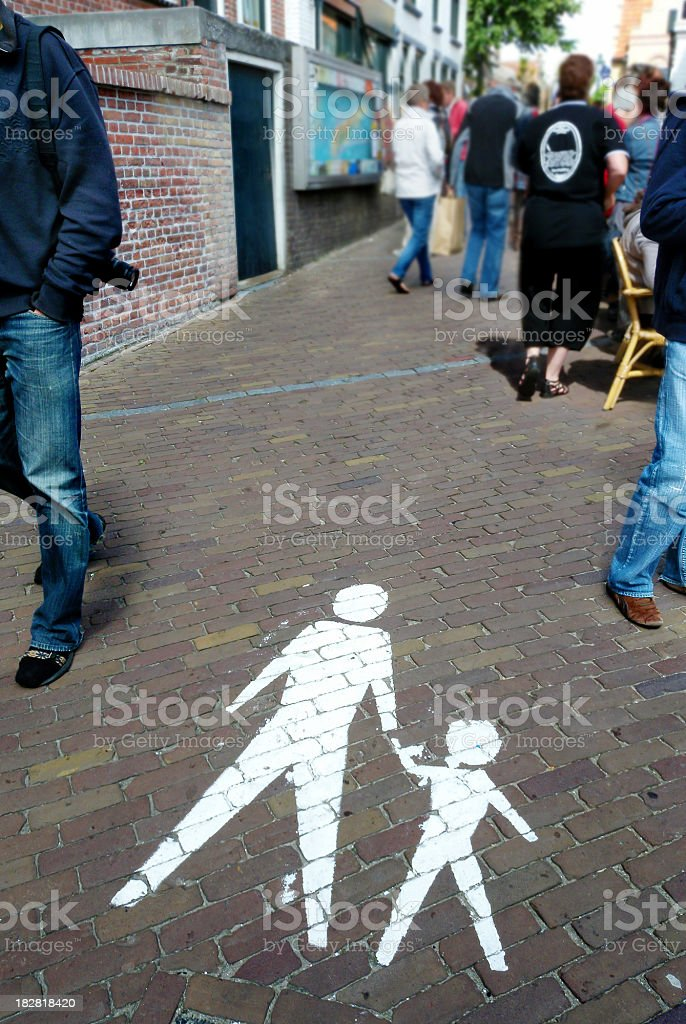pedestrian sign in front of a street witch walking people royalty-free stock photo