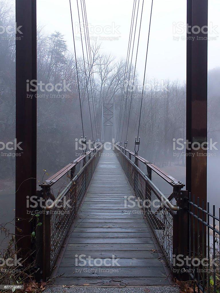 Pedestrian suspension bridge over river stock photo