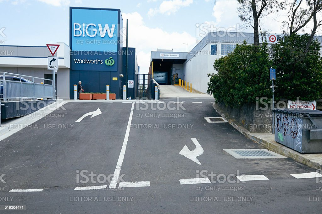 Pedestrian walking under Big W sign stock photo