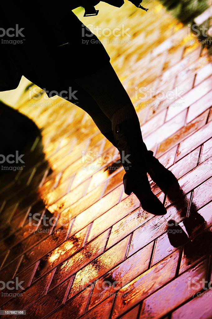 Pedestrian with bags on sidewalk in rain royalty-free stock photo