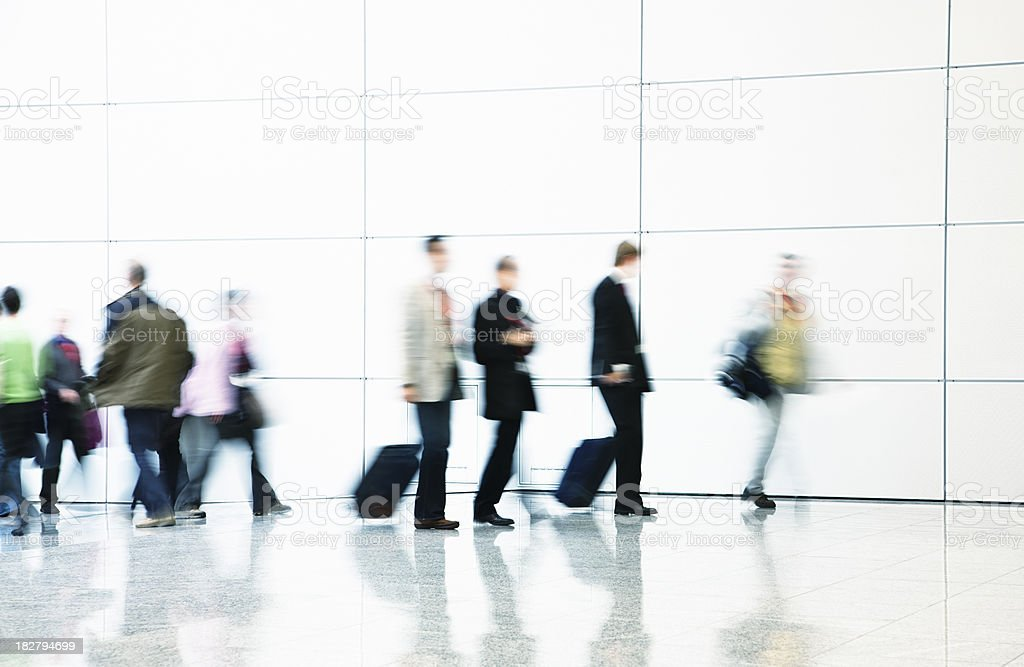 Pedestrians and Business Commuters Walking Down Hallway, Blurred Motion royalty-free stock photo