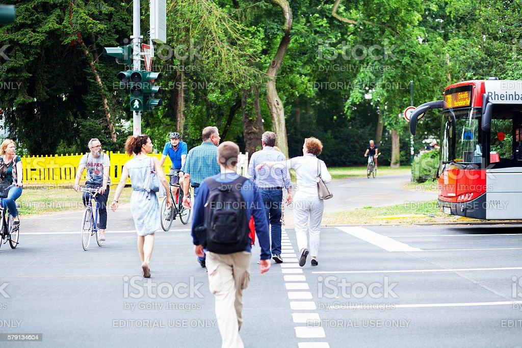 Pedestrians and cyclist on crosswalk stock photo