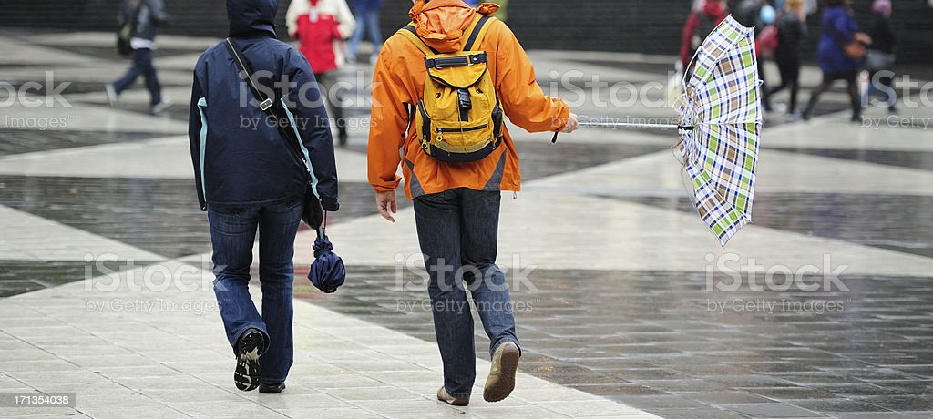 Pedestrians and umbrella in hard wind royalty-free stock photo