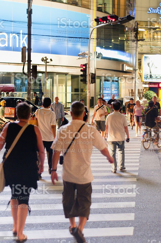 Pedestrians Crossing A Busy Street At Night royalty-free stock photo