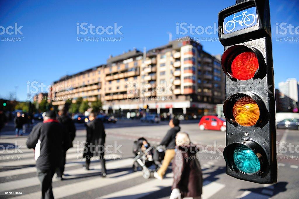 Pedestrians crossing street, bike traffic light