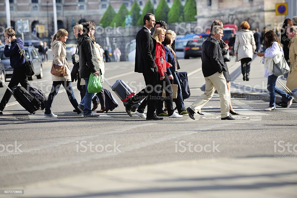 Pedestrians crossing street, traffic in background stock photo