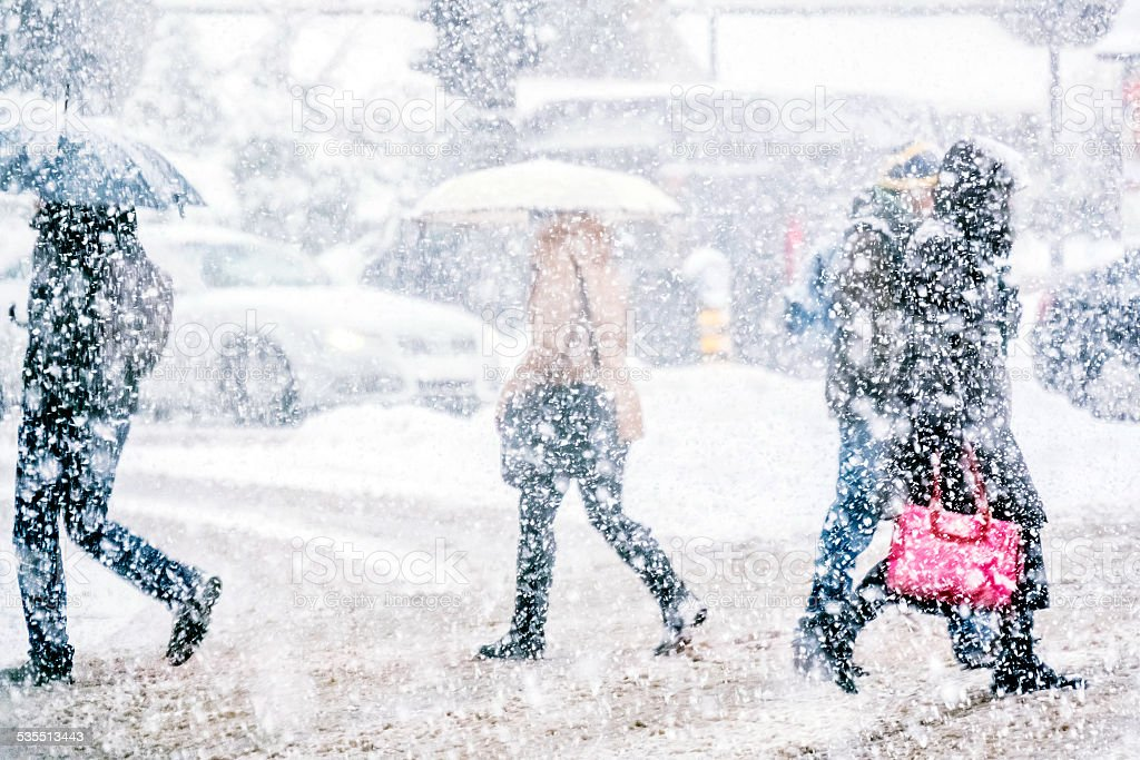 Pedestrians crossing the street on a snowy day stock photo