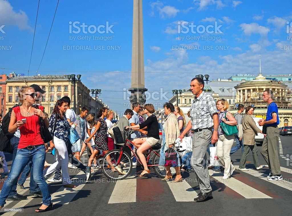 pedestrians crossing the street sunlit stock photo
