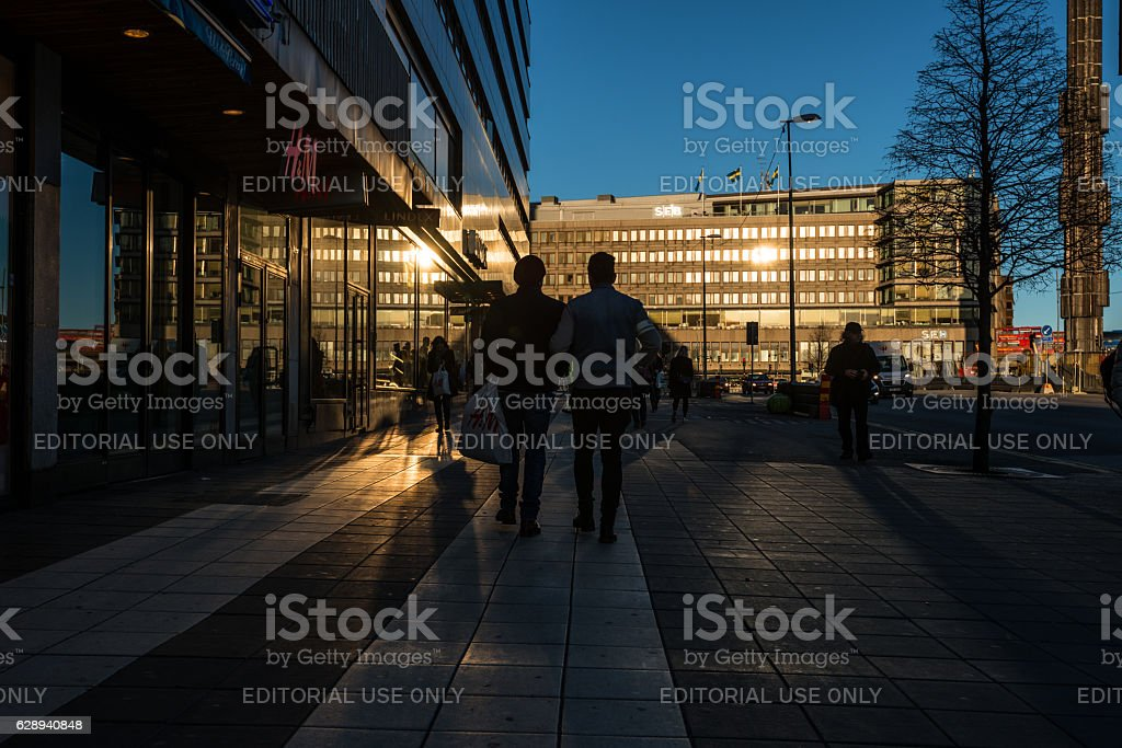 Pedestrians in silhouette, sunset in Stockholm stock photo