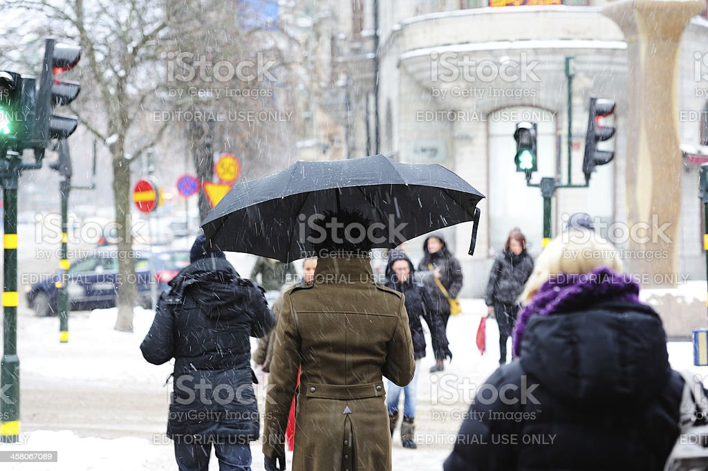 Pedestrians on zebra crossing. It's snowing. royalty-free stock photo