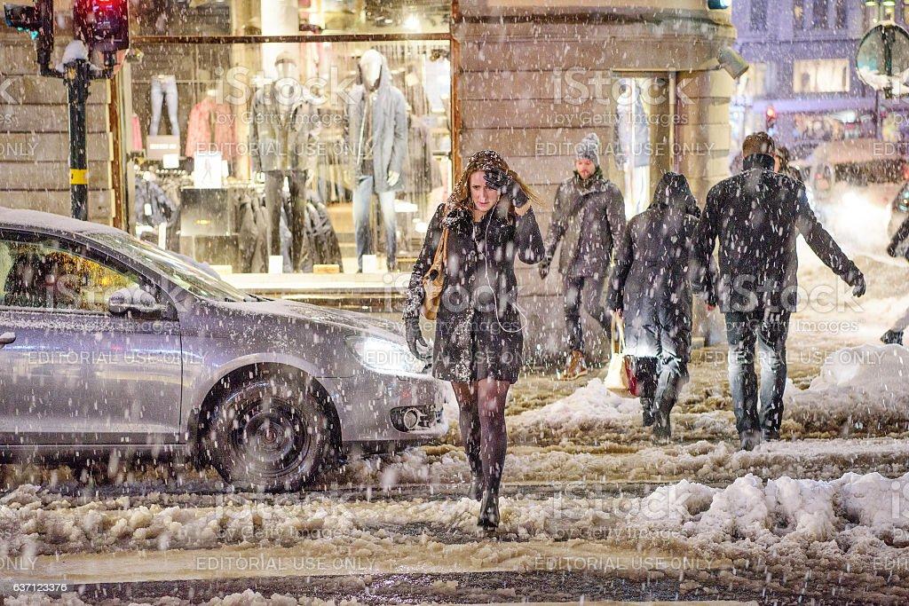 Pedestrians on zebra crossing. It's snowing. stock photo