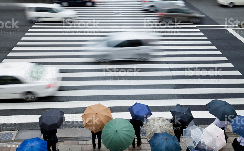 Pedestrians waiting to cross a busy road on a rainy day stock photo