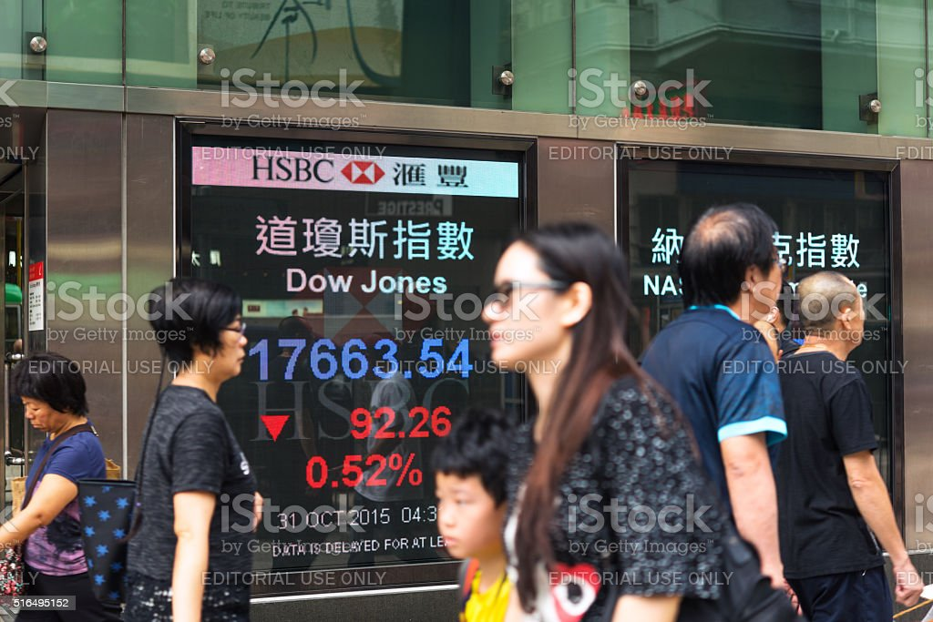 Pedestrians walk past a financial display board in Hongkong stock photo
