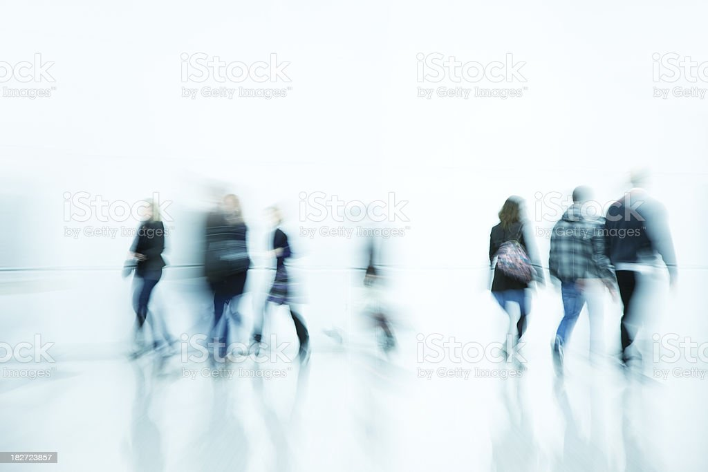 Pedestrians Walking Down Bright White Hallway, Blurred Motion royalty-free stock photo