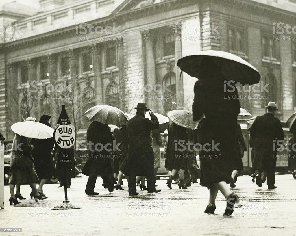 Pedestrians walking in rain in New York City, (B&W) stock photo