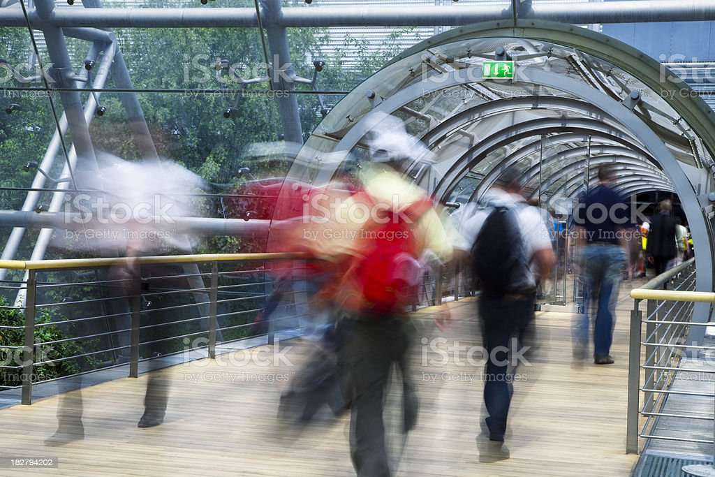 Pedestrians Walking Through Glass Tunnel, Blurred Motion stock photo