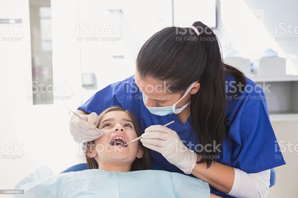 Pediatric dentist using dental explorer and angled mirror stock photo