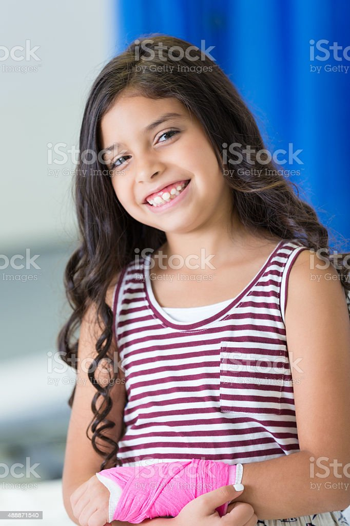 Pediatric patient with injured arm smiling in hospital ER stock photo