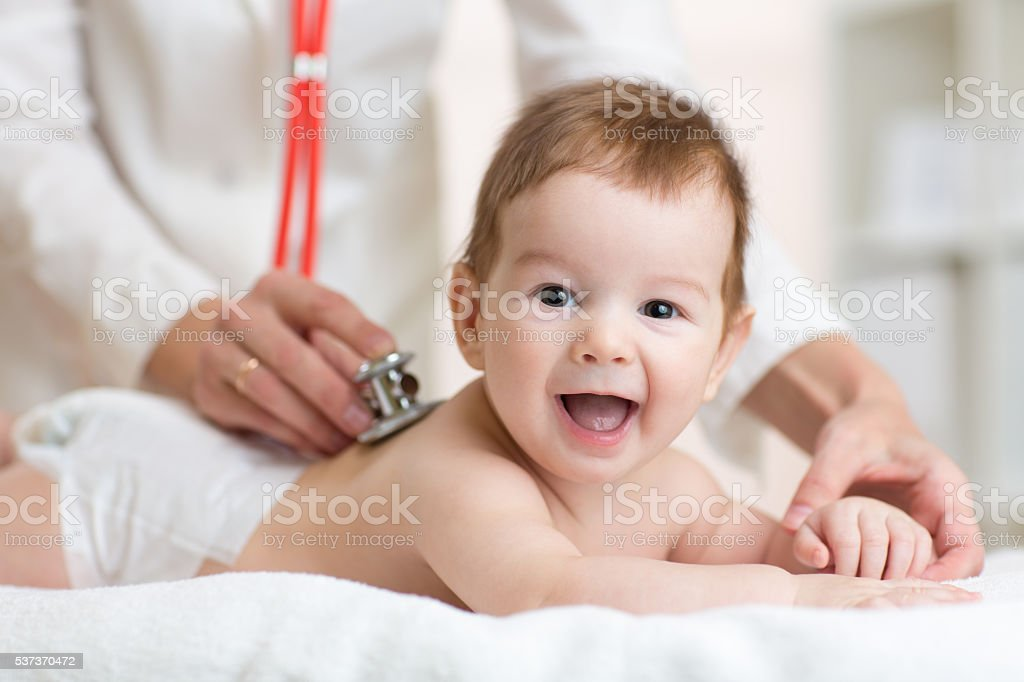 Pediatrician doctor examines baby with stethoscope checking heart beat. stock photo