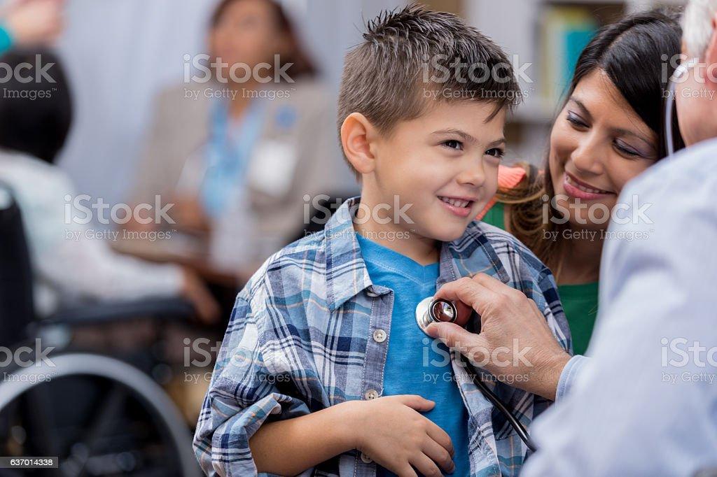 Pediatrician examines young male Hispanic patient stock photo