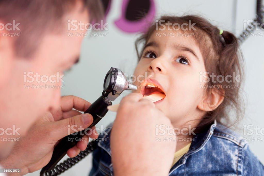 Pediatrician examining a little girl's throat stock photo