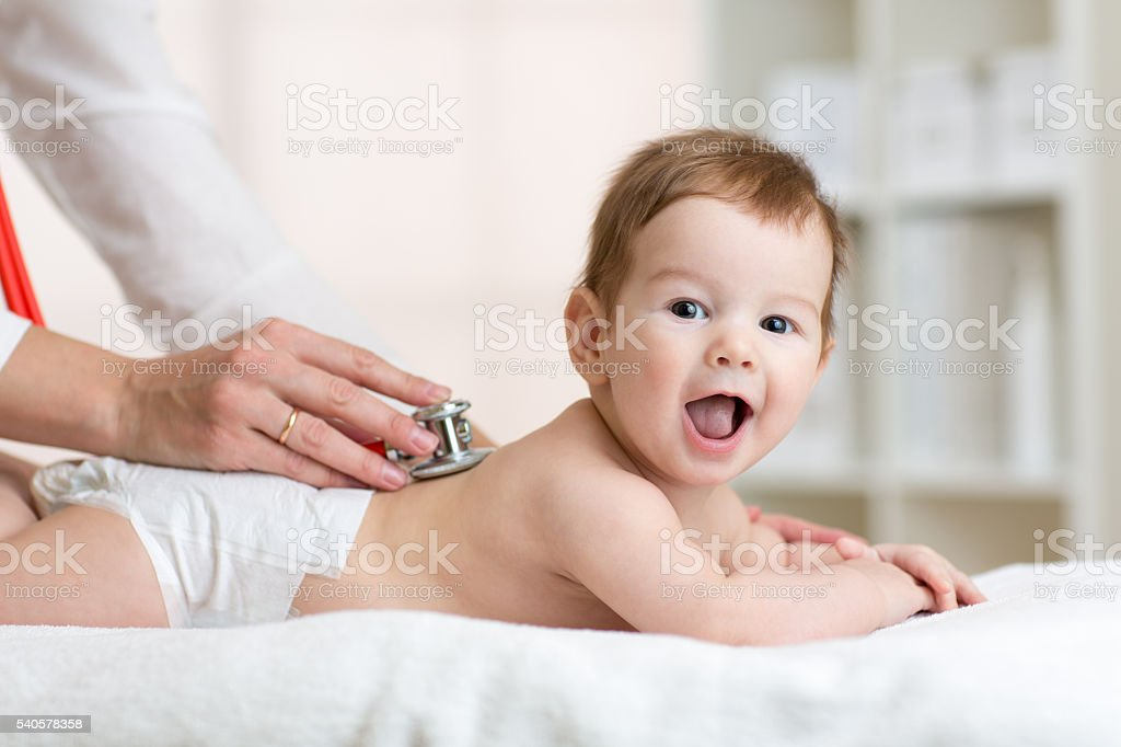 Pediatrician examining baby. Doctor using stethoscope listen to kid back stock photo