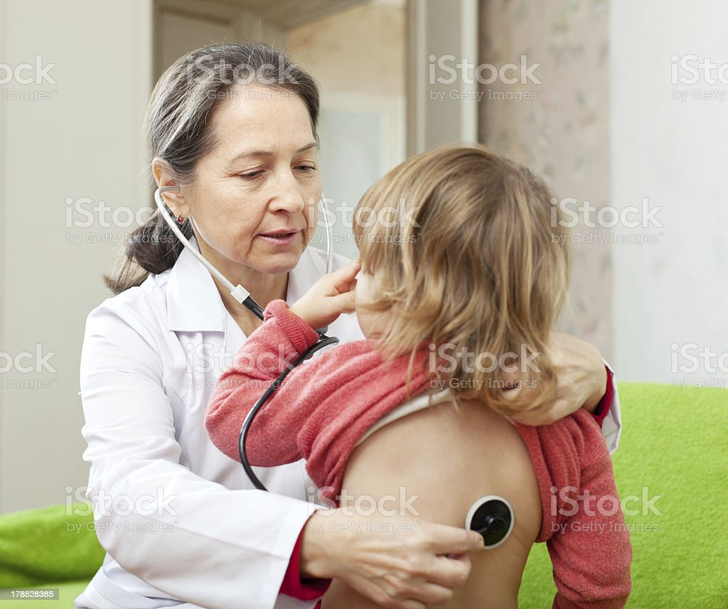pediatrician  examining child with  stethoscope royalty-free stock photo
