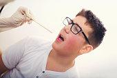 Pediatrician examining teenager throat with tongue depressor