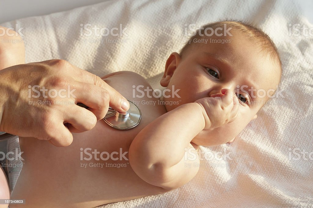 Pediatrician exams infant with stethoscope stock photo