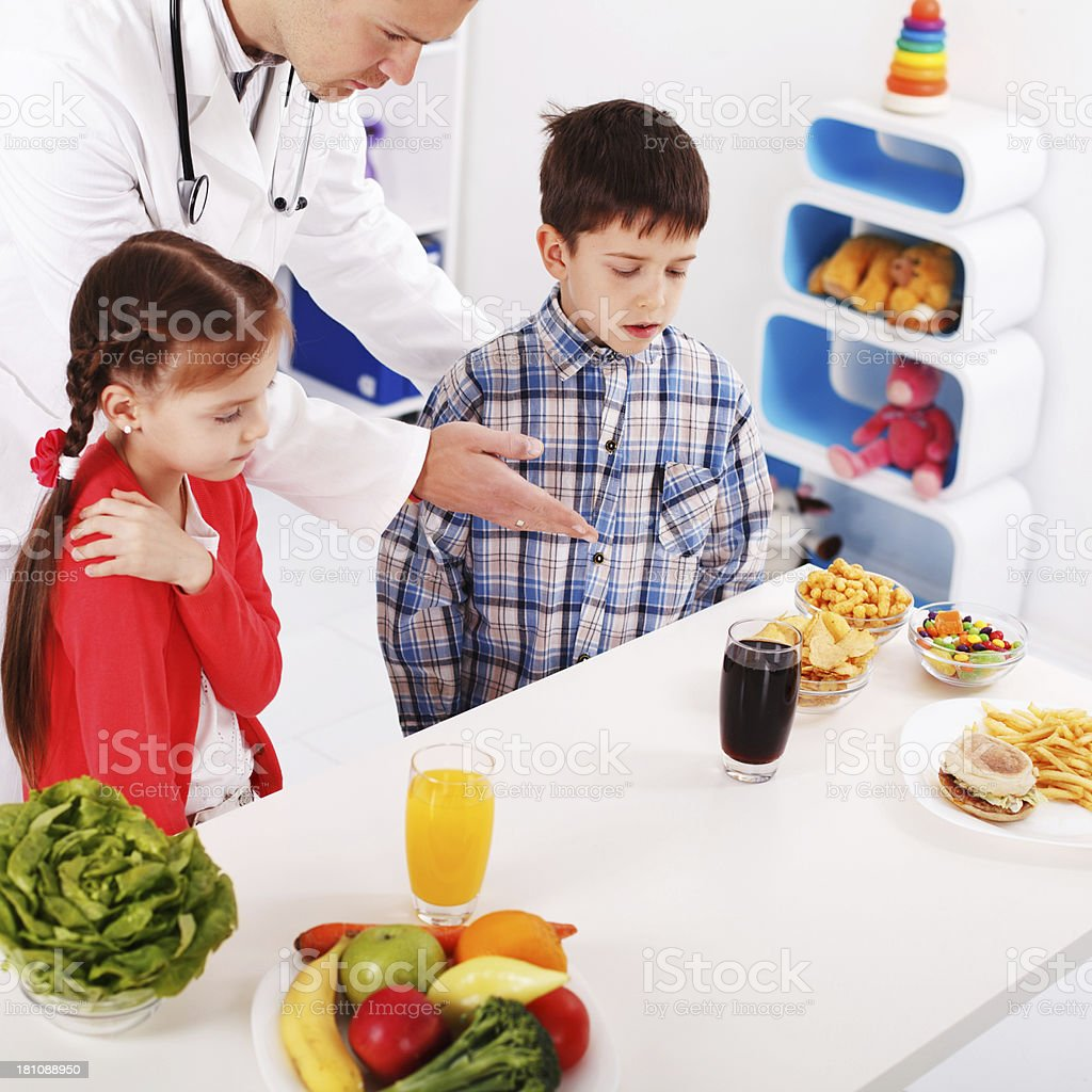 Pediatrician explaining children about healthy and unhealthy eat royalty-free stock photo