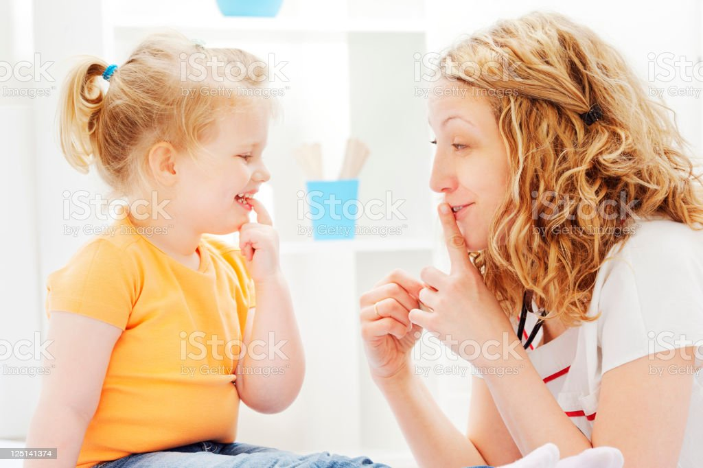 Pediatrician friendly chatting with little girl patient royalty-free stock photo