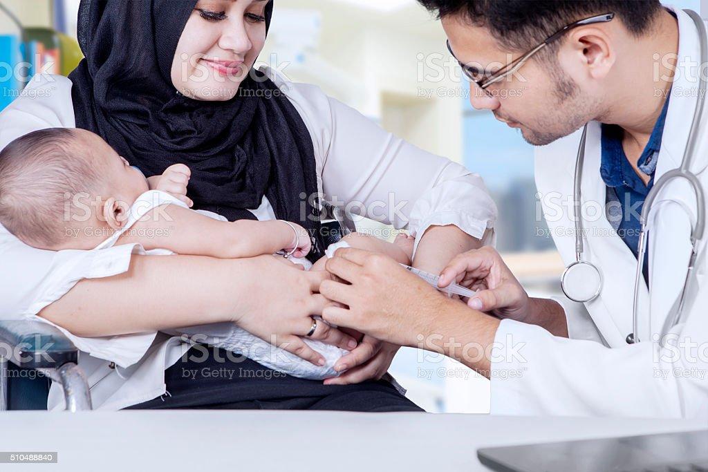 Pediatrician giving vaccine to baby boy stock photo
