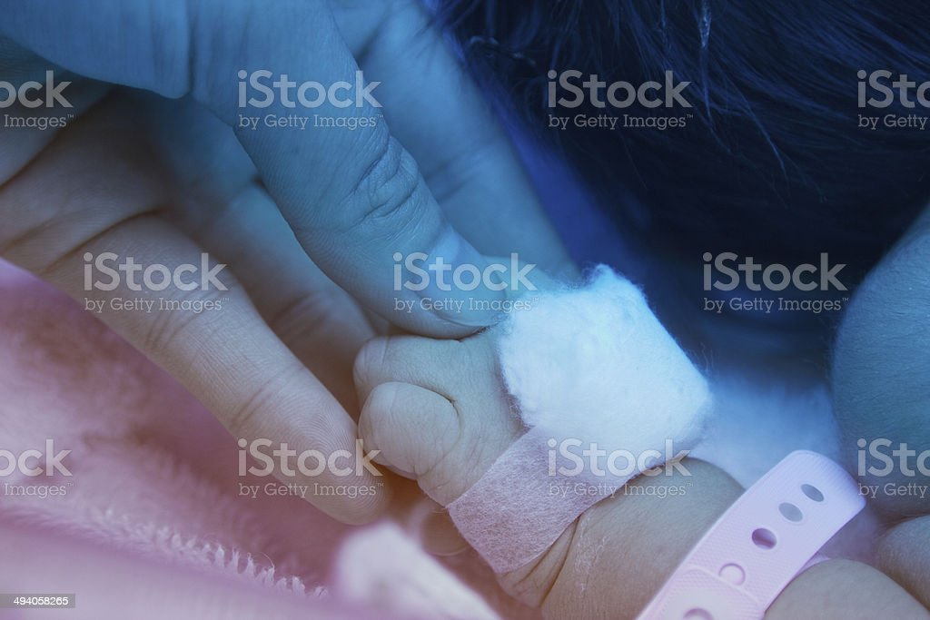 Pediatrician hold a baby's hand, under ultraviolet lamp stock photo