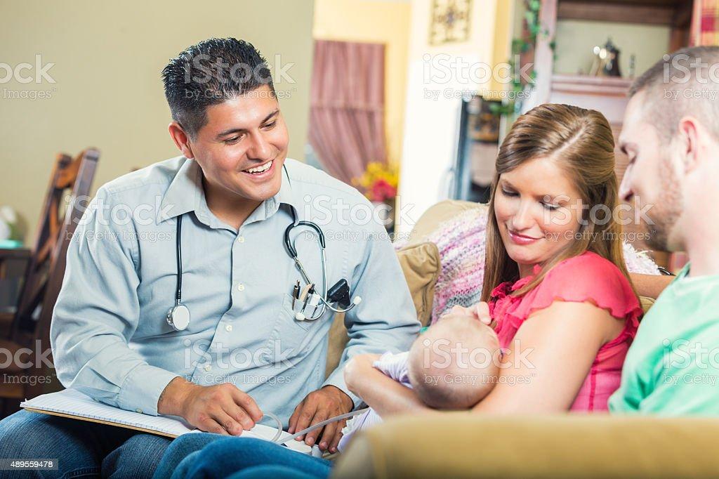 Pediatrician making house call for sick newborn baby stock photo