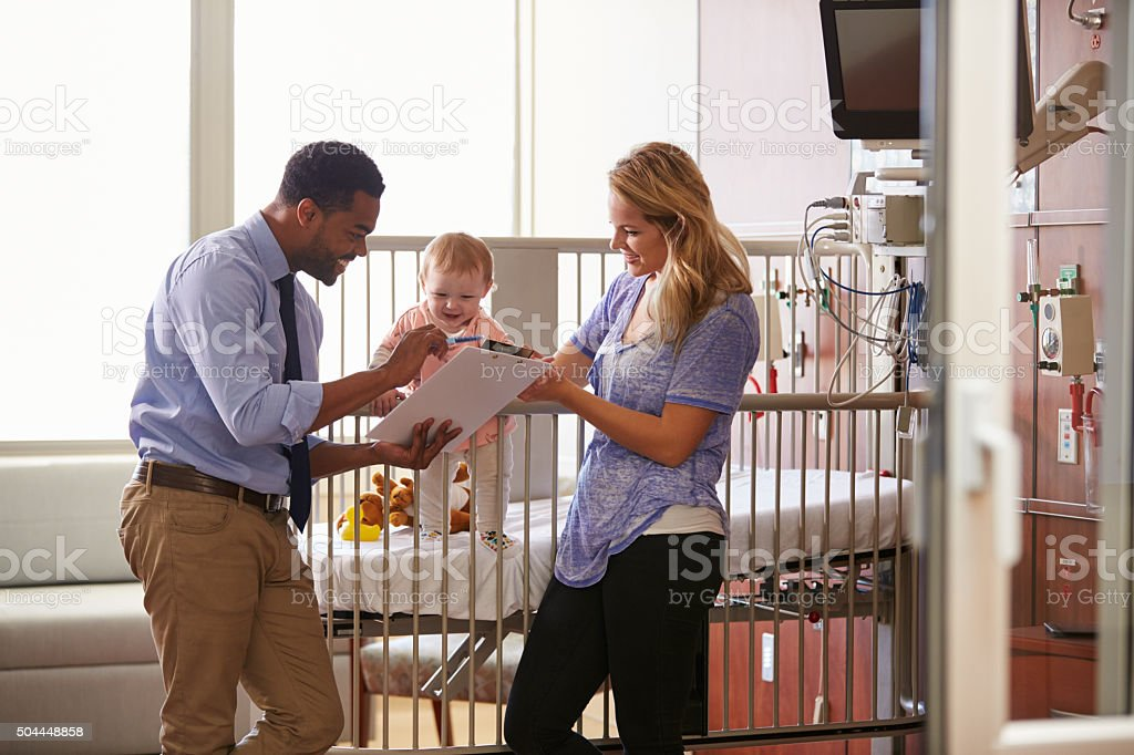 Pediatrician Visiting Mother And Child In Hospital Bed stock photo
