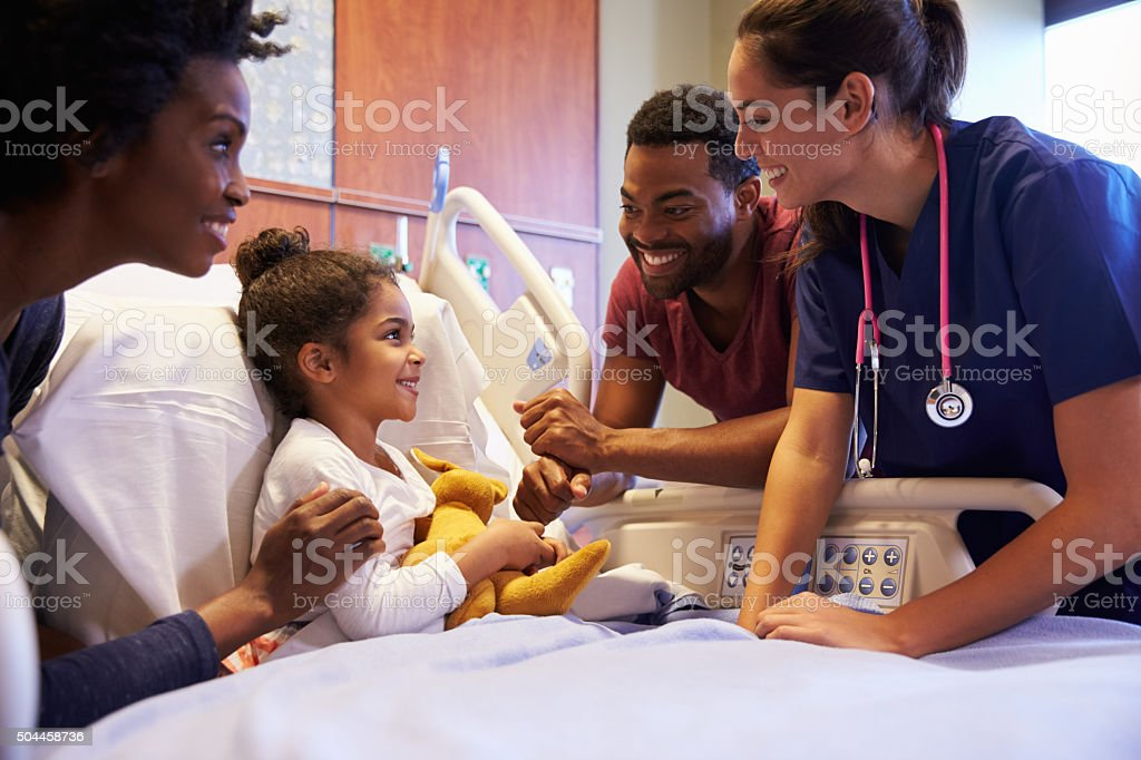 Pediatrician Visiting Parents And Child In Hospital Bed stock photo