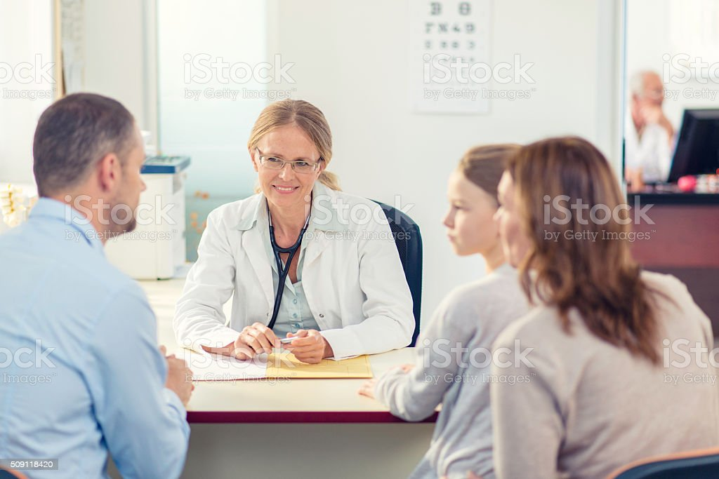 Comforting young female doctor with patient stock photo