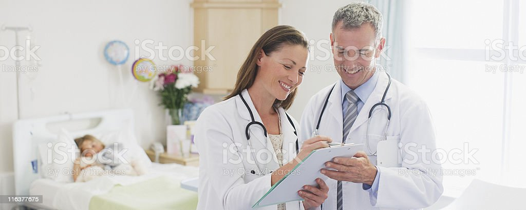 Pediatricians reviewing patients medical record in hospital royalty-free stock photo