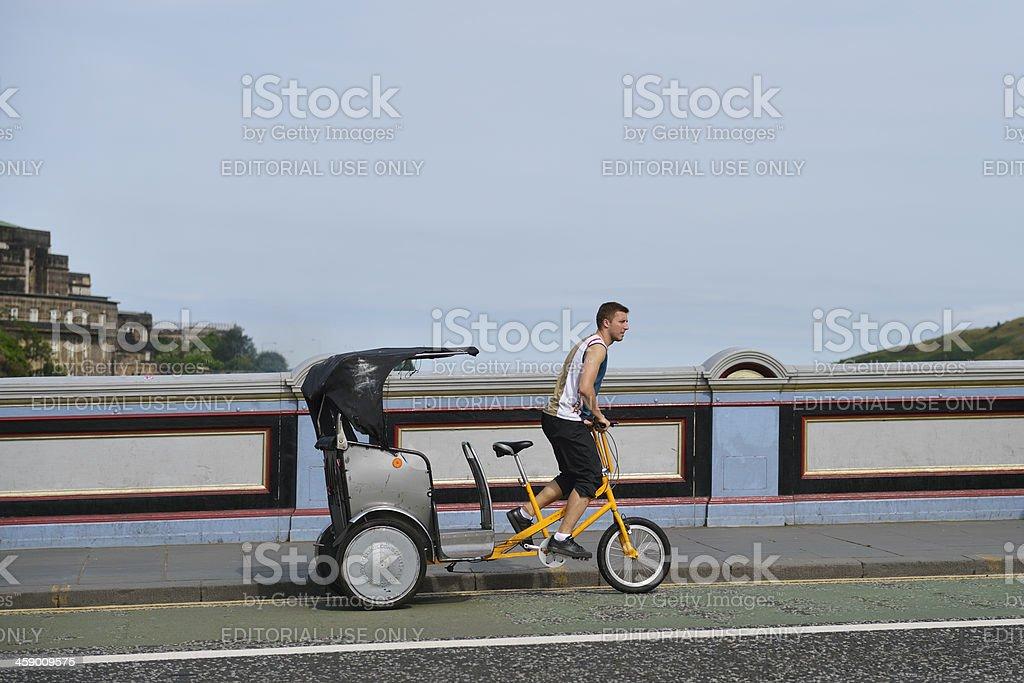 Pedicab driver working the streets of Edinburgh stock photo