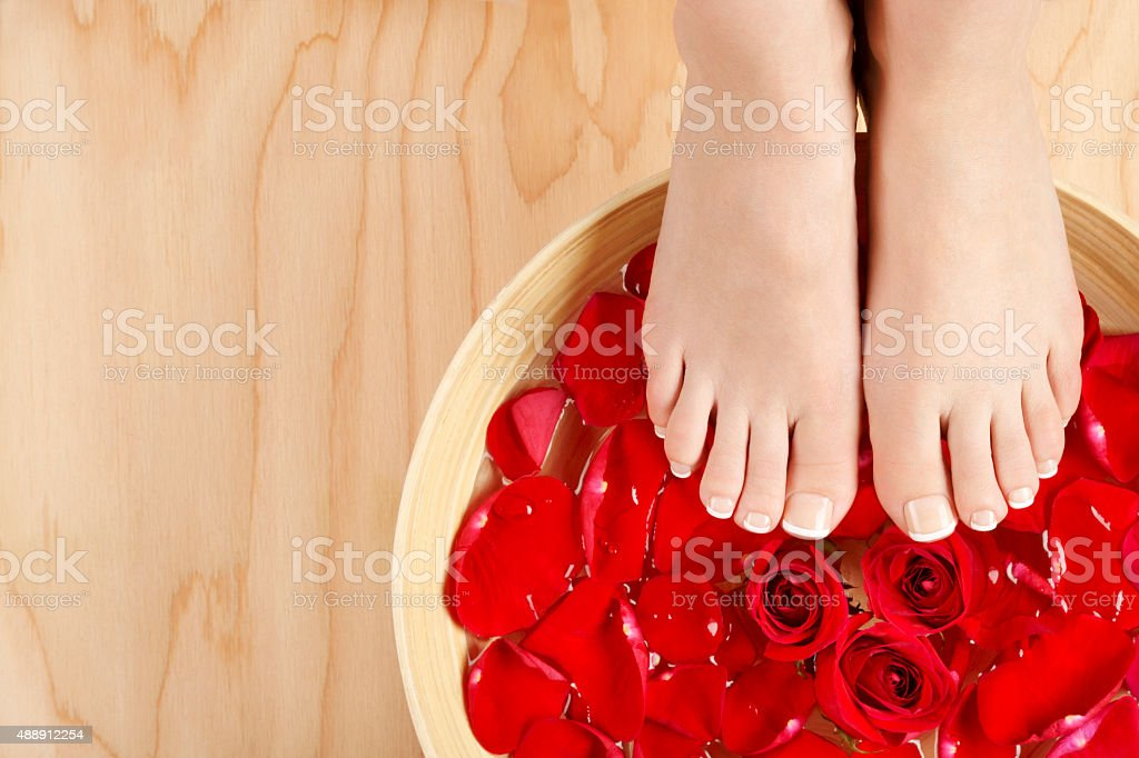 Pedicure Spa Treatment with Red Roses Wood Background royalty-free stock photo