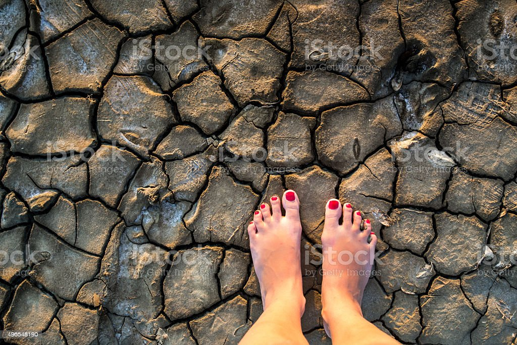 Pedicured feet on dried soil royalty-free stock photo