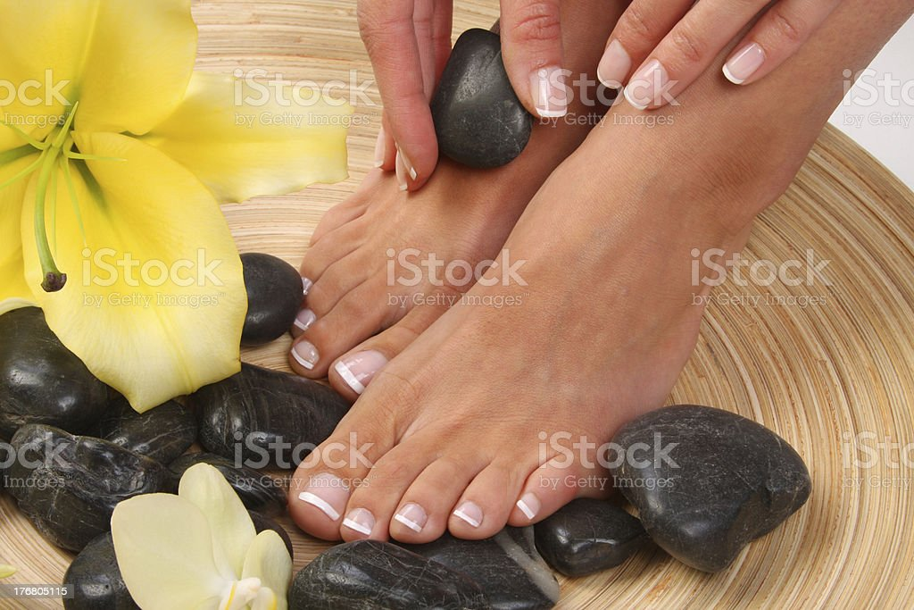 Pedicured feet with stones and flowers royalty-free stock photo
