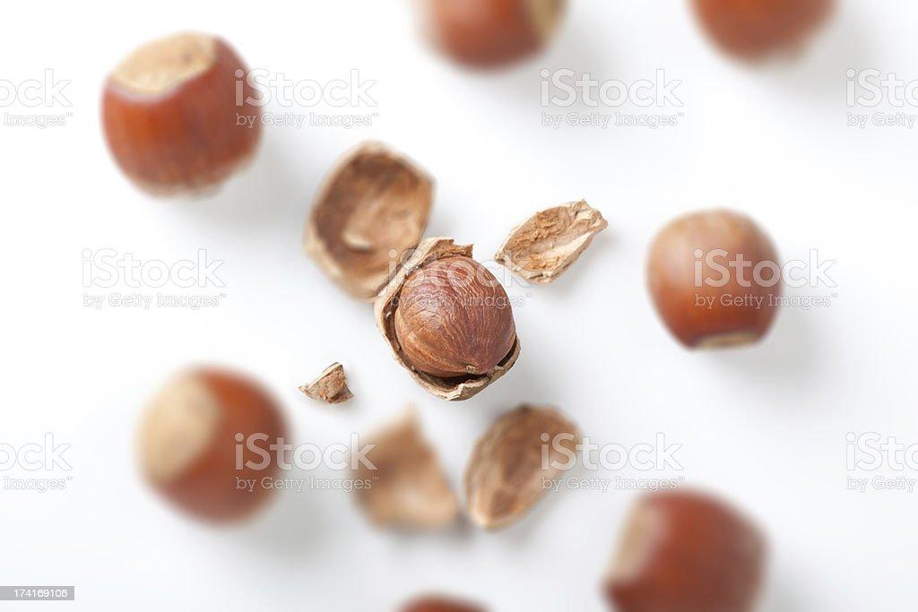 peeled hazelnut among unpeeled, isolated on white royalty-free stock photo