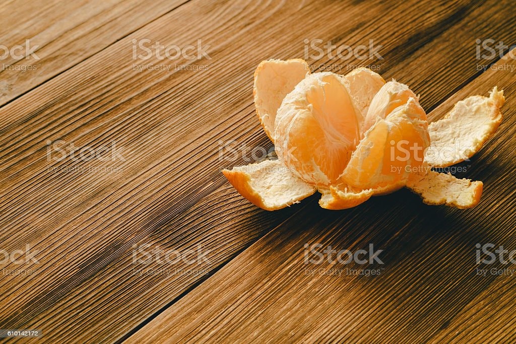 Peeled Mandarin on a wooden table stock photo
